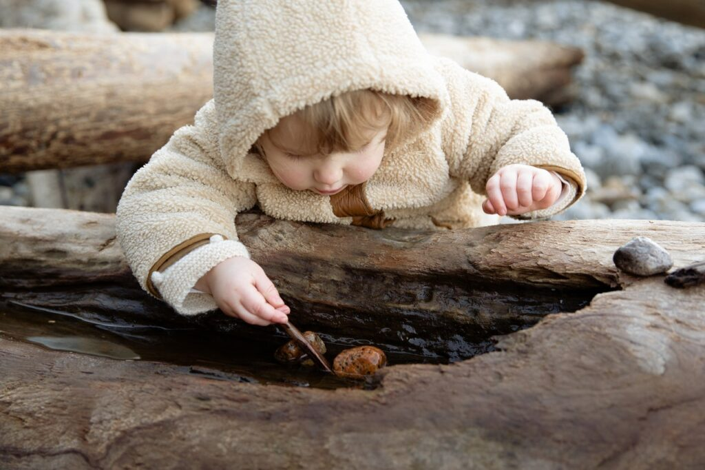 cute-little-girl-playing-with-stones-on-log-on-shore_Photo by Tatiana Syrikova